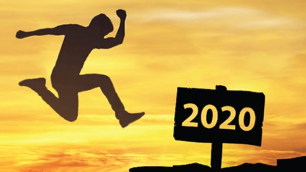 "A silhouette of a person jumping toward a sign saying ""2020"" with a sunrise"