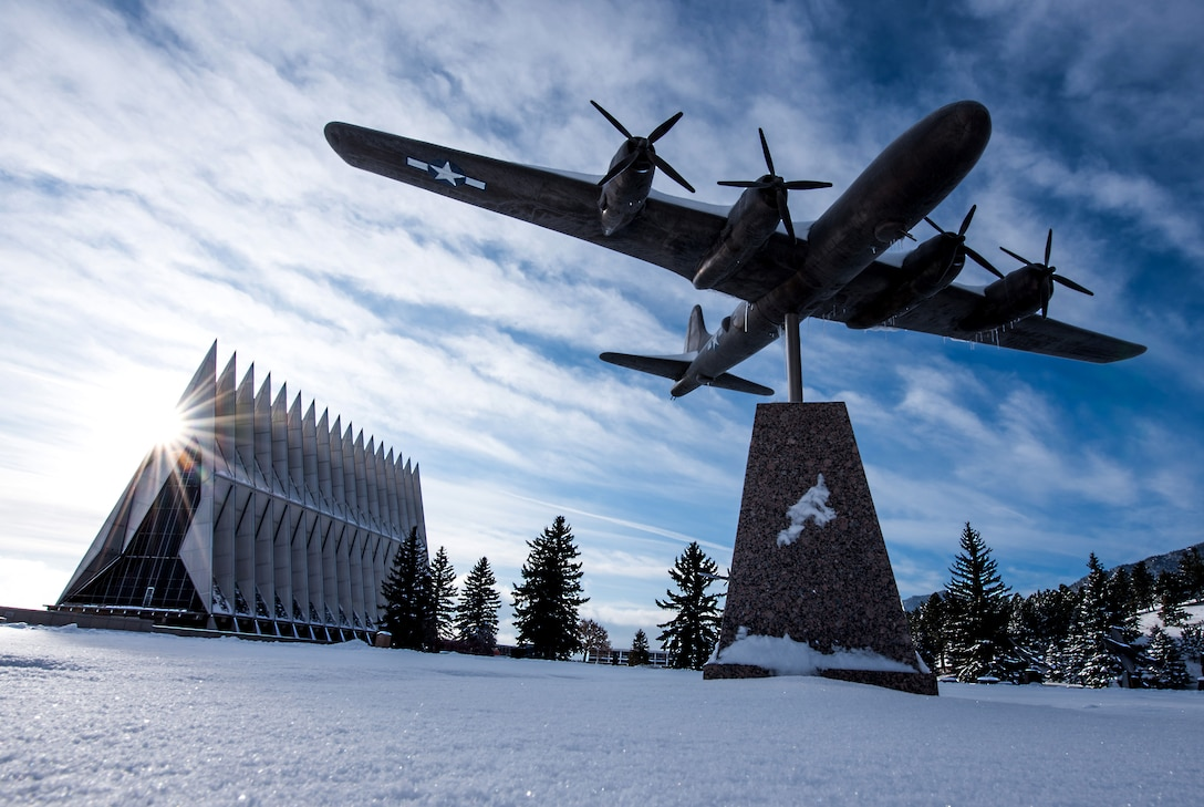 Static shot of a vintage aircraft at the top of a pedestal with the U.S. Air Force Academy chapel in the background.