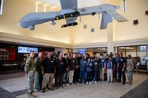 432nd Wing/432nd Air Expeditionary Wing Airmen members, Iron Sharpens Iron Mentoring youth and mentors take a group photo under an MQ-1 Predator during their visit to Creech Air Force Base