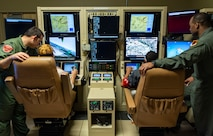 Capt. Marcus, left, 432nd Wing executive officer, and Lt. Col.  Michawn, right, 17th Attack Squadron director of operations, teach local youth as they sit in the pilot's seat of an MQ-9 Reaper in a flight simulator at Creech Air Force Base