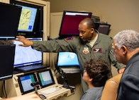 Lt. Col.  Michawn, 17th Attack Squadron director of operations, teaches Iron Sharpens Iron Mentoring youth how to fly the MQ-9 Reaper in a flight simulator at Creech Air Force Base