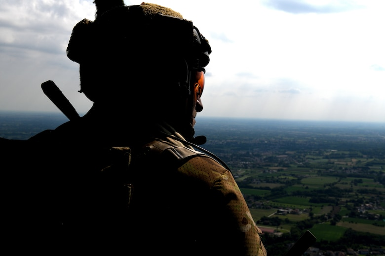 A pararescueman from the 57th Rescue Squadron looks out of an HH-60G Pave Hawk during Operation Porcupine over a military training area in Osoppo, Italy, June 30, 2020. Operation Porcupine demonstrated the unique capabilities of the 31st Operations Group which host all assets needed to conduct a combat search and rescue mission. (U.S. Air Force photo by Senior Airman Caleb House)