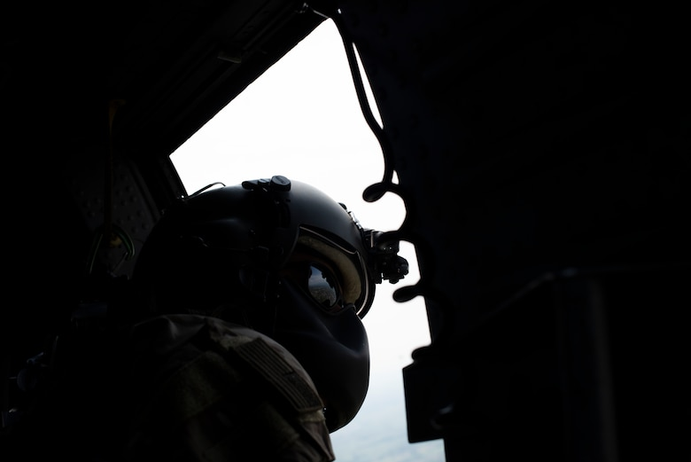 An Airman from the 56th Rescue Squadron looks out of an HH-60G Pave Hawk during Operation Porcupine over a military training area in Osoppo, Italy, June 30, 2020. Operation Porcupine is a combat search and rescue exercise requiring Aviano's 510th Fighter Squadron, 56th and 57th Rescue Squadron, and 606th Air Control Squadron to work together to accomplish the mission.  (U.S. Air Force photo by Senior Airman Caleb House)