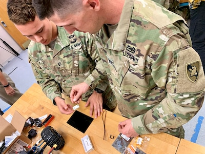 Hackathon - West Point Cadet Hunter Hill and Capt. Mark Lesak, Center for Mechanical Engineering instructor and Army Cyber Institute researcher, work together to design and provide technical solutions to challenges for equipment used by USASOC. USASOC technology developers, West Point faculty from Center for Innovation and Engineering and the Robotics Research Center, staff from the Army Cyber Institute, and Cadets teamed up to pursue a rapid design and prototyping effort.