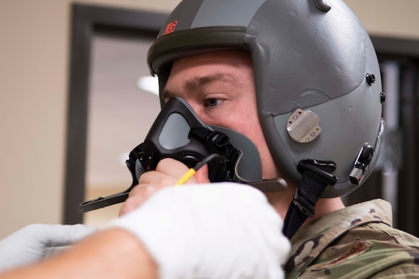 Photo of Airman being fit for helmet.