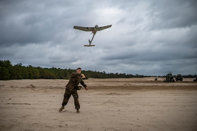 Cpl. Nicholas Whisenhunt, an engineer equipment operator with Special Purpose Marine Air-Ground Task Force - Southern Command, launches an RQ-11B Raven during a field exercise at Camp Lejeune, North Carolina, June 11, 2020. The FEX provides the Marines and Sailors the opportunity to stay proficient with their equipment and refine their tactical skill sets. SPMAGTF-SC is poised to conduct crisis response, general engineering training and theater security cooperations alongside partner nation militaries in Latin America and the Caribbean. Whisenhunt is a native of Keizer, Oregon. (U.S. Marine Corps photo by Sgt. Andy O. Martinez)