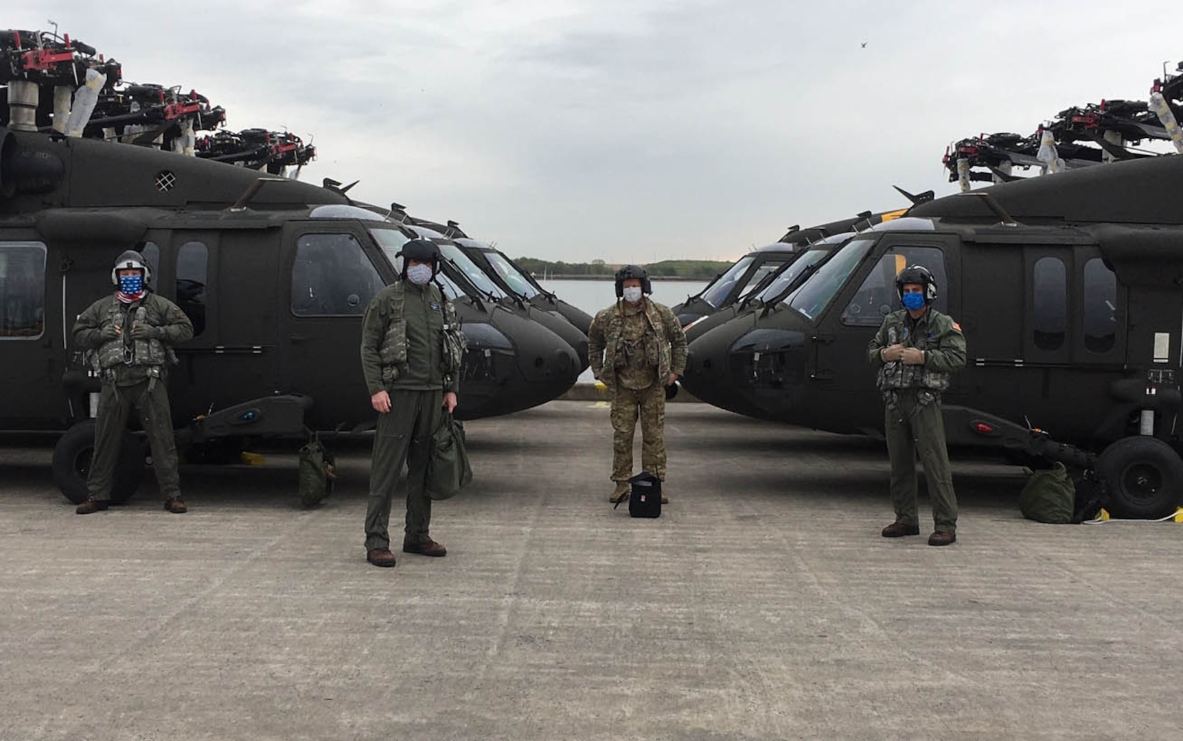 Four soldiers in flight suits stand in front of UH-60 Blackhawk helicopters.
