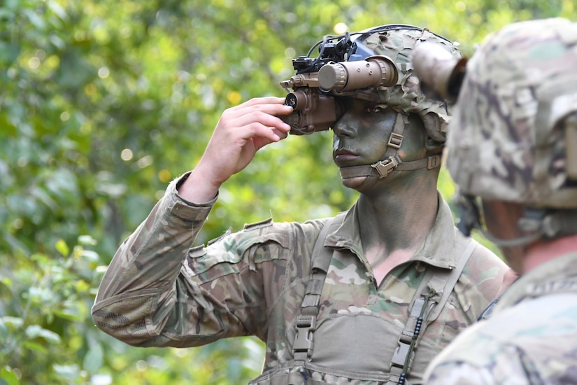 A soldier adjusts his binoculars.