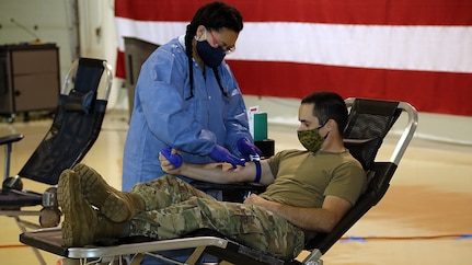 Alaska Army National Guard Capt. James Tollefson, an operations plans officer with Joint Task Force-Alaska, donates blood at the Guard Armory on Joint Base Elmendorf-Richardson, May 26, 2020. Blood donation centers have been impacted by a lack of donors during the COVID-19 pandemic, while the need for blood, plasma and platelets continue to be critically needed for many medical services. (U.S. Army National Guard photo by Sgt. Seth LaCount/Released)