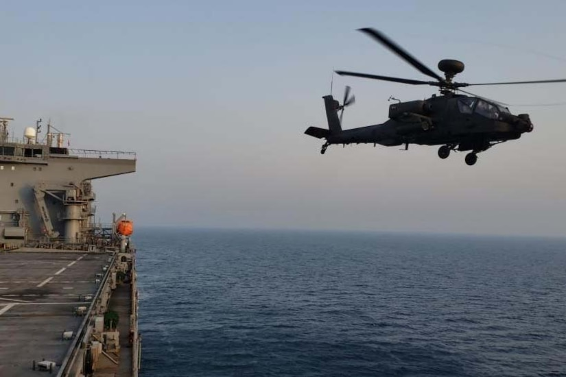 A helicopter flies alongside a ship.