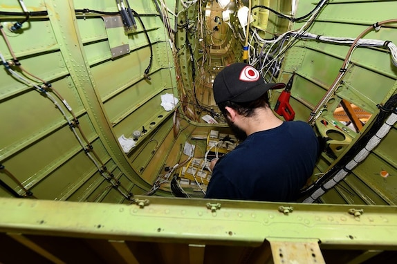 John Farhat, aircraft electrical mechanic III with Amentum, at the Corpus Christi Army Depot, Texas, installs arc 220 wiring for the UH-60L communications system inside the aircraft tail section. This is the first aircraft (8BZ32) to be painted using 100% class N (non-chromate) primers on the interior and exterior. Corpus Christi is setting the standard for both military and commercial industry to follow.  (Photo by Ervey Martinez)