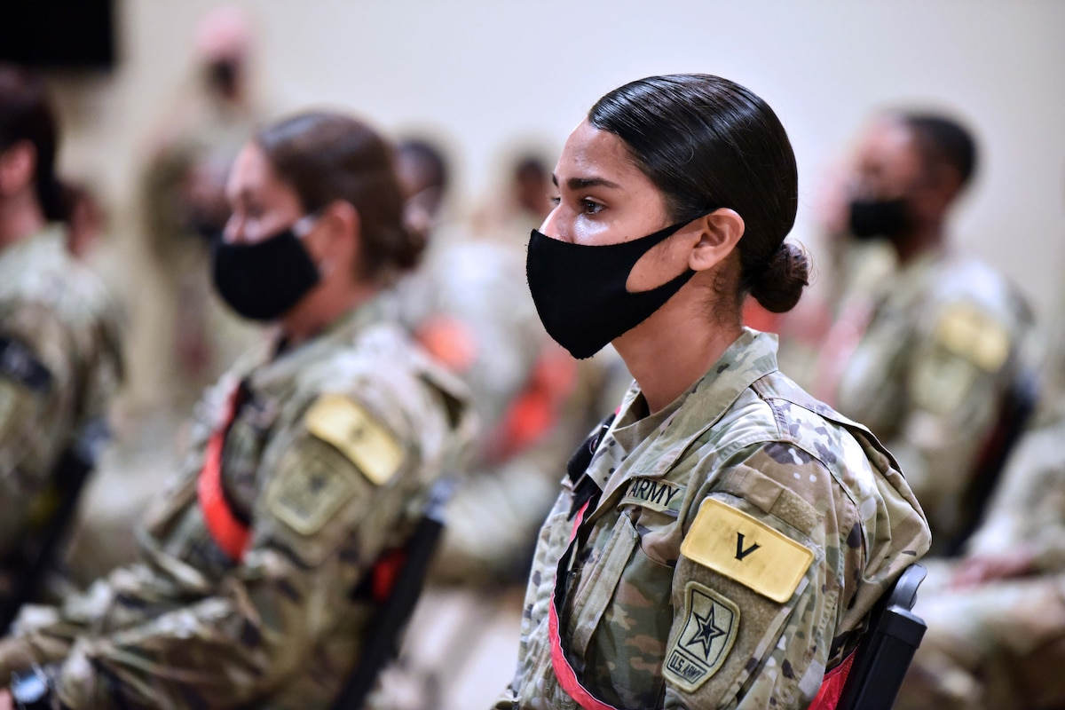 Several soldiers wearing masks listen to a senior officer during a forum.