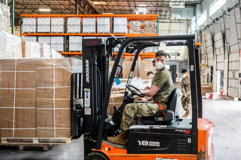 A soldier drives a forklift lifting a pallet of boxes.