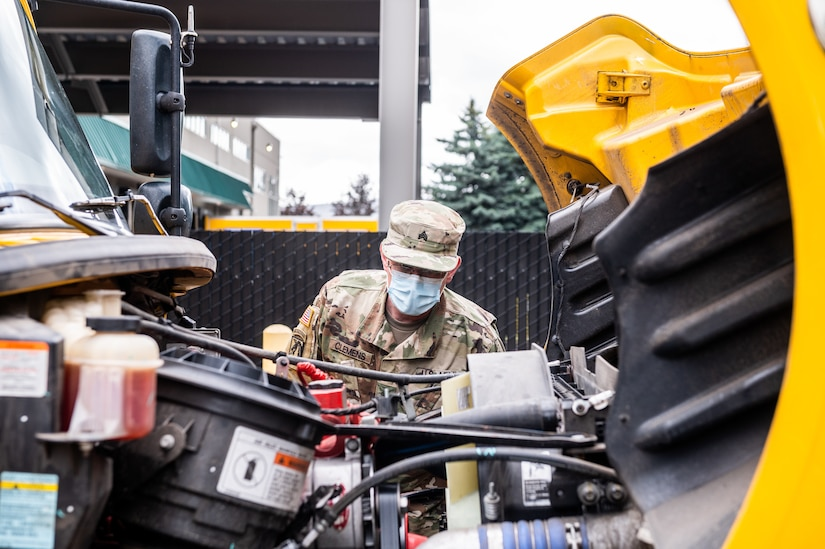 A soldier checks under the hood of a truck.