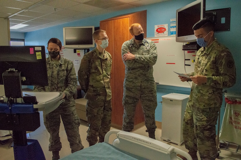 Four military doctors wearing masks stand in a pediatrics ward as one of them checks a monitor.