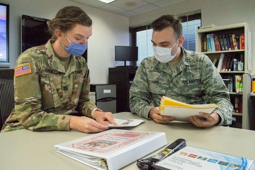 Two military doctors wearing face masks sit at a table comparing notes.