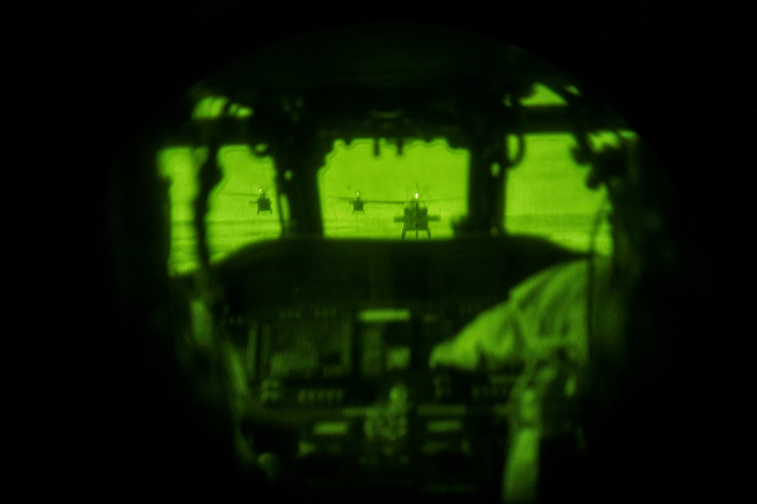 Three Army helicopters fly as seen through night vision googles.