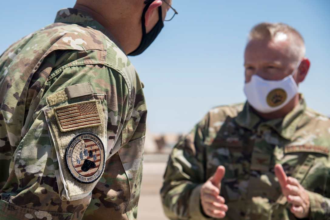 """Gen. Arnold W. Bunch Jr., left, Air Force Materiel Command commander, speaks with Col. Frank Marconi, 635th Materiel Maintenance Group commander, during Bunch's Basic Expeditionary Airfield Resources Base tour, June 29, 2020, at the 635th MMG on Holloman Air Force Base, N.M. The patch worn on Bunch's arm is a """"BEAR"""" patch sporting an American flag in the background. BEAR base is accountable for the storage, inspection, repair, deployment and assets belonging to AFMC. (U.S. Air Force photo by Senior Airman Collette Brooks)"""