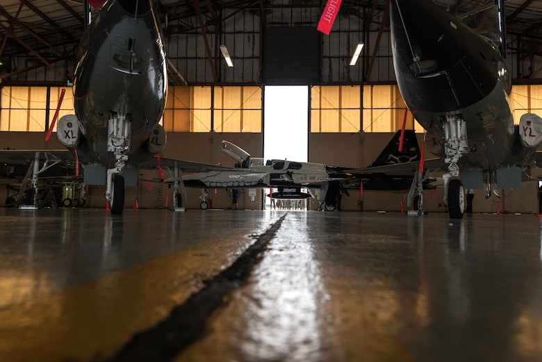 "The hangar doors open to reveal the T-38C Talon aircraft, painted with a first assignment instructor pilot theme, as pilots and maintainers alike watch eagerly from outside, June 26, 2020 at Laughlin Air Force Base, Texas. ""The best part was seeing Valentin's face and how excited all the pilots were,"" Juan Gonzalez, 47 MXD corrosion control work lead, said. ""Col. Jones complimented our work and that meant a great deal to us. We feel proud of the work we did."" (U.S. Air Force Photo by Senior Airman Anne McCready)"