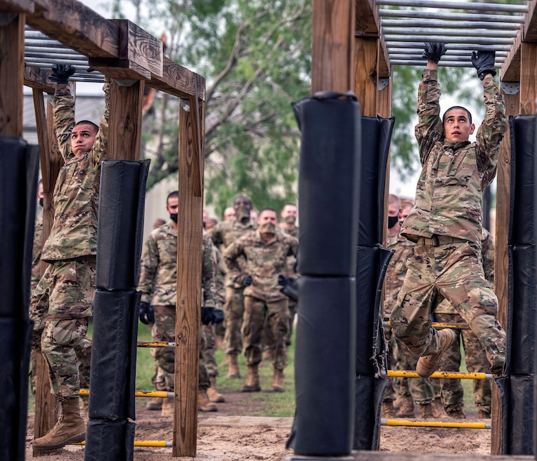 Nicolas (left) and his brother Daniel (right) Hughes, U.S. Air Force basic training trainee, run through an obstacle course May 21 at Joint Base San Antonio-Chapman Annex.