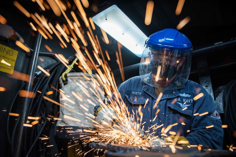 Sparks fly while a welder works on metal.
