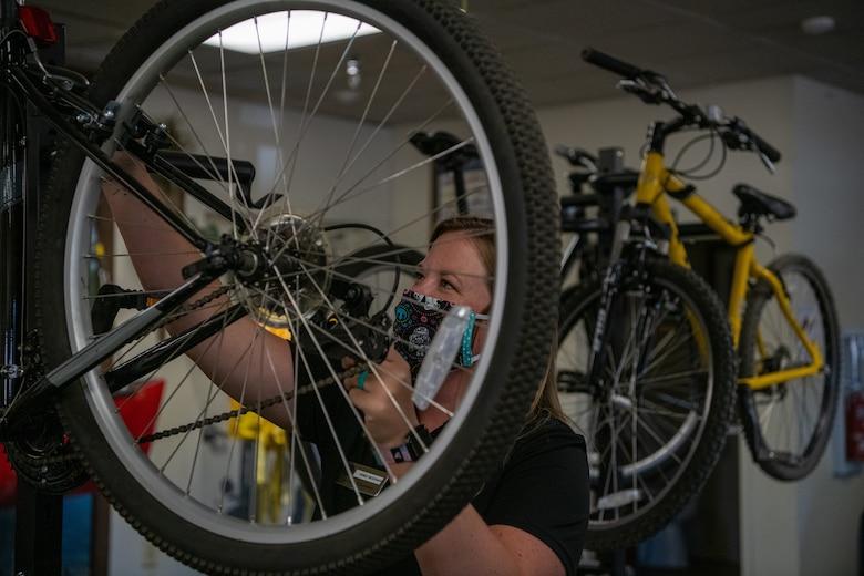Andi Hickman, Outdoor Recreation associate, adjusts mountain bike brakes June 16, 2020, at Luke Air Force Base, Ariz.