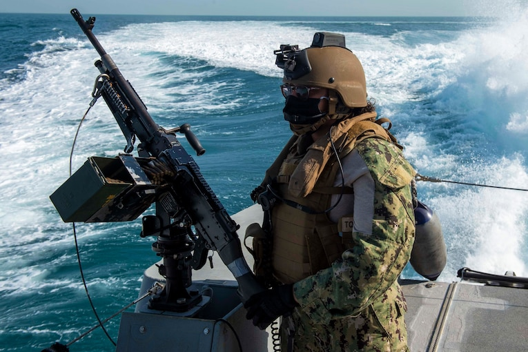 A sailor stands by a machine gun on a boat.