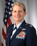 White, blonde female in blues uniform, Colonel, standing in front of flag