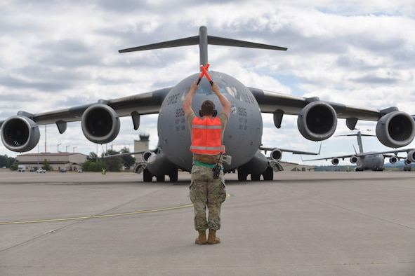 A 721st Aircraft Maintenance Squadron Airman marshalls a C-17 Globemaster III aircraft following the first-ever operational use of the Negatively Pressurized Conex to transport 12 COVID-19 patients to Ramstein Air Base, Germany, July 1, 2020. The NPC is the latest isolated containment chamber developed to transport up to 28 individuals with infectious diseases. (U.S. Air Force photo by Airman 1st Class John R. Wright)