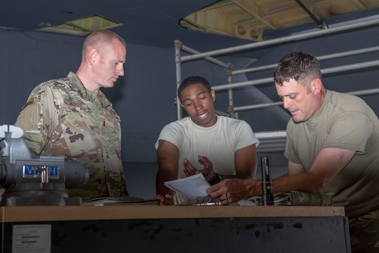Photo of Airmen speaking around a table.