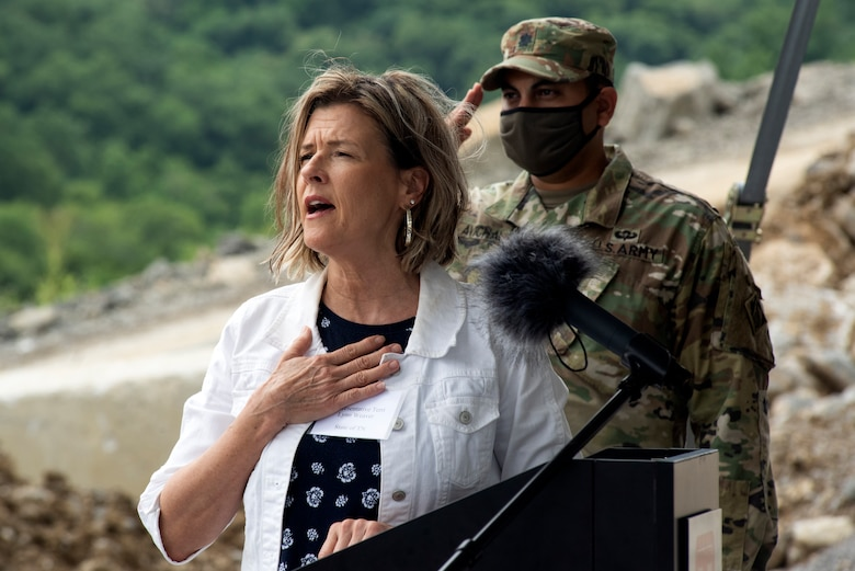 Tennessee District 40 Rep. Terri Lynn Weaver sings the National Anthem at the Center Hill Lake Auxiliary Dam July 1, 2020 during a ceremony celebrating the completion of the last phase of repairs for the $353 million Center Hill Dam Safety Rehabilitation Project. The U.S. Army Corps of Engineers Nashville District recently finished constructing a roller compacted concrete berm to reinforce the auxiliary dam at Center Hill Lake, a secondary earthen embankment that fills a low area in the landscape just east of the main dam. (USACE Photo by Lee Roberts)