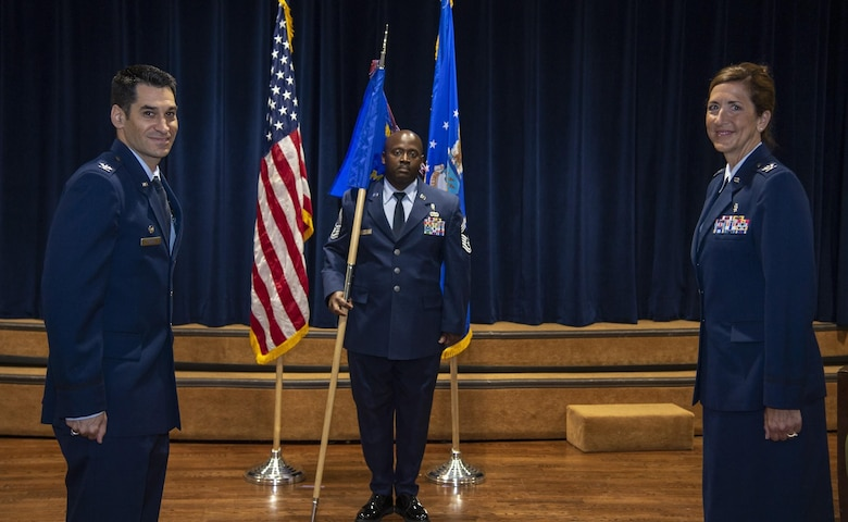 U.S. Air Force Col. Benjamin Robins, 6th Air Refueling Wing commander, ceremoniously passes the 6th Medical Group (MDG) guidon to Col. Courtney Finkbeiner, the in-coming 6th MDG commander during a change of command ceremony at MacDill Air Force Base, Fla., June 26, 2020.