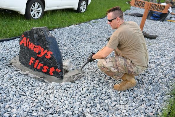 Photo shows an Airmen shoveling cement around a boulder.