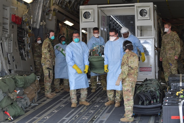 Airmen assigned to the 313th Expeditionary Operations Support Squadron transfer a COVID-19 patient following the first-ever operational use of the Negatively Pressurized Conex to transport 12 COVID-19 patients aboard a C-17 Globemaster III aircraft at Ramstein Air Base, Germany, July 1, 2020. The NPC is the latest isolated containment chamber developed to transport up to 28 individuals with infectious diseases. (U.S. Air Force photo by Airman 1st Class John R. Wright)