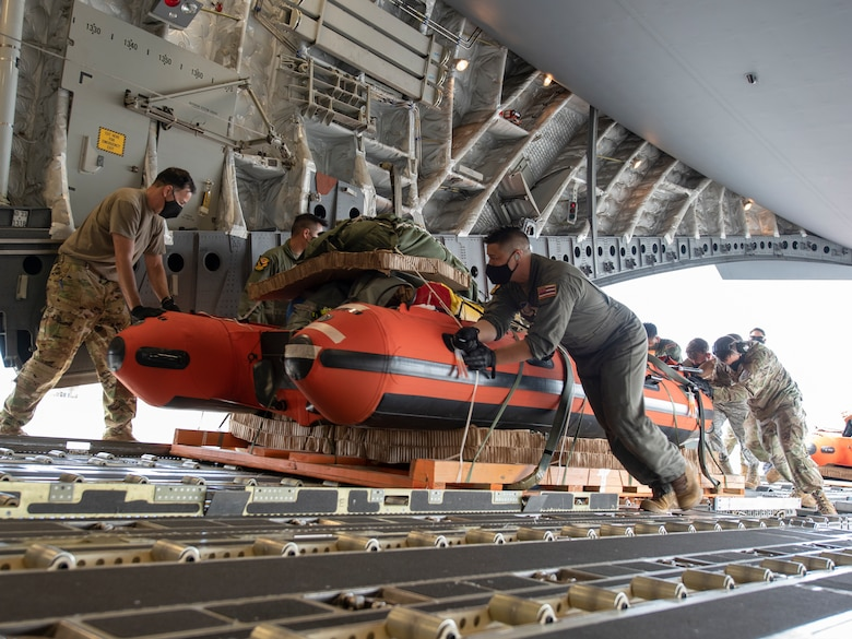 U.S. Air Force Airmen, assigned to the Hawaii Air National Guard, load pararescuemen equipment onto a C-17 Globemaster III, May 26, 2020 at Joint Base Pearl Harbor-Hickam. The Airmen pre-rigged the C-17 in order to be able to quickly respond to astronaut rescue in the Pacific region in support of a manned space flight launch on May 30. (U.S. Air National Guard photo by Senior Airman Orlando Corpuz)