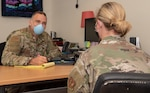 U.S. Air Force Major Jason Mitchell, 52nd Medical Operations Squadron mental health flight commander and psychologist, left, and Major Cara Grausam, 52nd MDOS mental health element chief and clinical social worker, demonstrate physical distancing and other COVID-19 precautions they are taking during meetings at Spangdahlem Air Base, Germany, May 18, 2020. During the COVID-19 pandemic, the 52nd MDOS is currently innovating new ways to provide care to the members of the 52nd Fighter Wing, one manner in which they are doing so is through telemedicine. (U.S. Air Force photo by Senior Airman Kyle Cope)