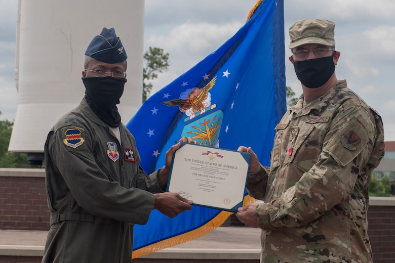 service member in flight suit presents service member in OCPs with Bronze Star Medal certificate.