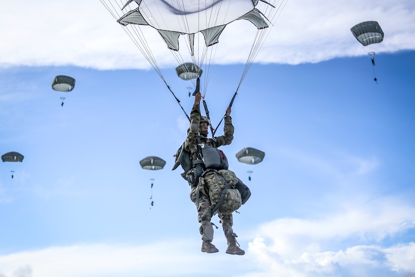 A soldier holds onto his parachute while descending in the blue sky, as other parachutes descend in the background.