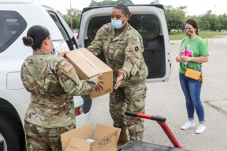 A soldier hands a cardboard box to another soldier standing by the open trunk of a vehicle as a civilian looks on.
