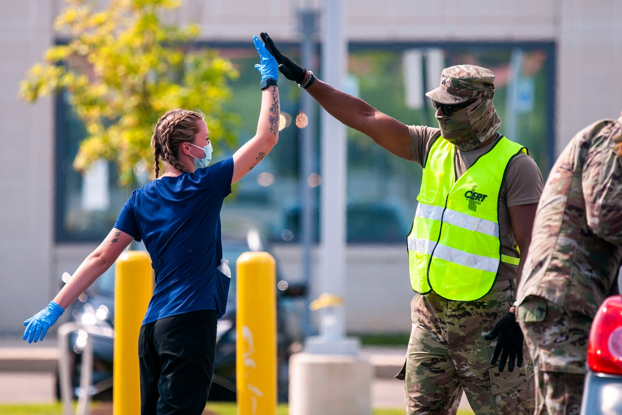 Guardsmen wearing protective gear high-five.