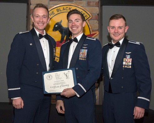 1st Lt David Schmitz (middle), receives his certificate of training during the 8th Fighter Squadron's F-16 Basic Course graduation on Holloman Air Force Base, N.M., Dec. 14, 2019. Schmitz was killed when his F-16 crashed during a routine training mission while stationed at Shaw AFB, S.C., June 30, 2020. (U.S. Air Force photo by Staff Sgt. Christine Groening)