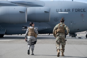 U.S. Air Force Airman 1st Class Stephanie DaSilva, left, 60th Security Forces Squadron installation entry controller, and Staff Sgt. Brenden Rinehart, 60th SFS patrolman, walk toward a C-17 Globemaster III May 16, 2020, during security check on the flight line at Travis Air Force Base, California. The C-17 is one of three aircraft assigned to Travis AFB and is often called upon to support mobility missions. (U.S. Air Force photo by Tech. Sgt. James Hodgman)