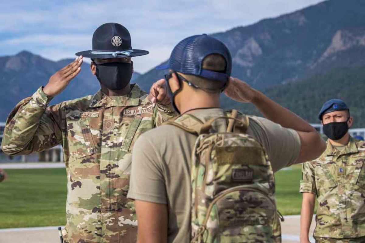 An airman salutes a cadet as another airman stands to the side; all three wear face masks.