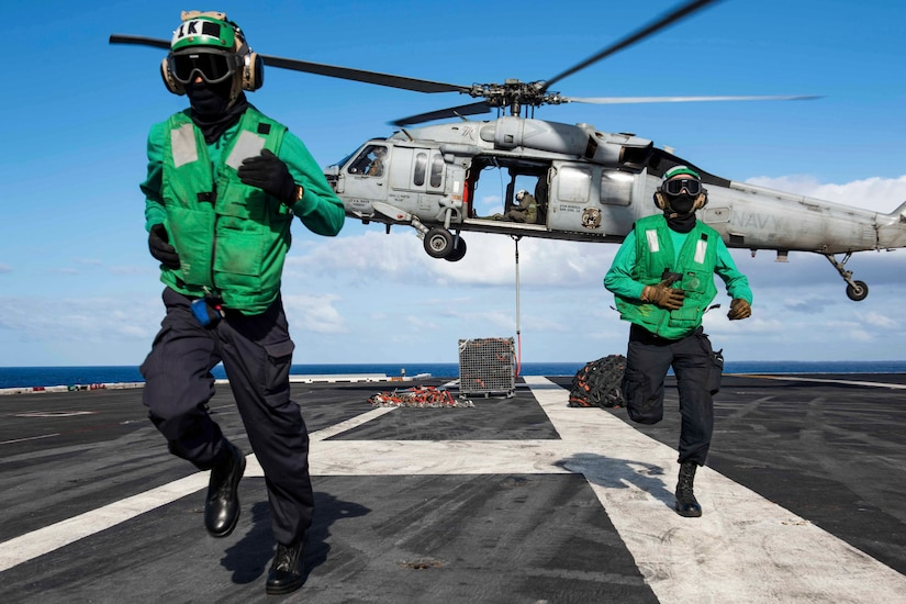 Two sailors run away from a helicopter that is lifting off from the deck of a ship.