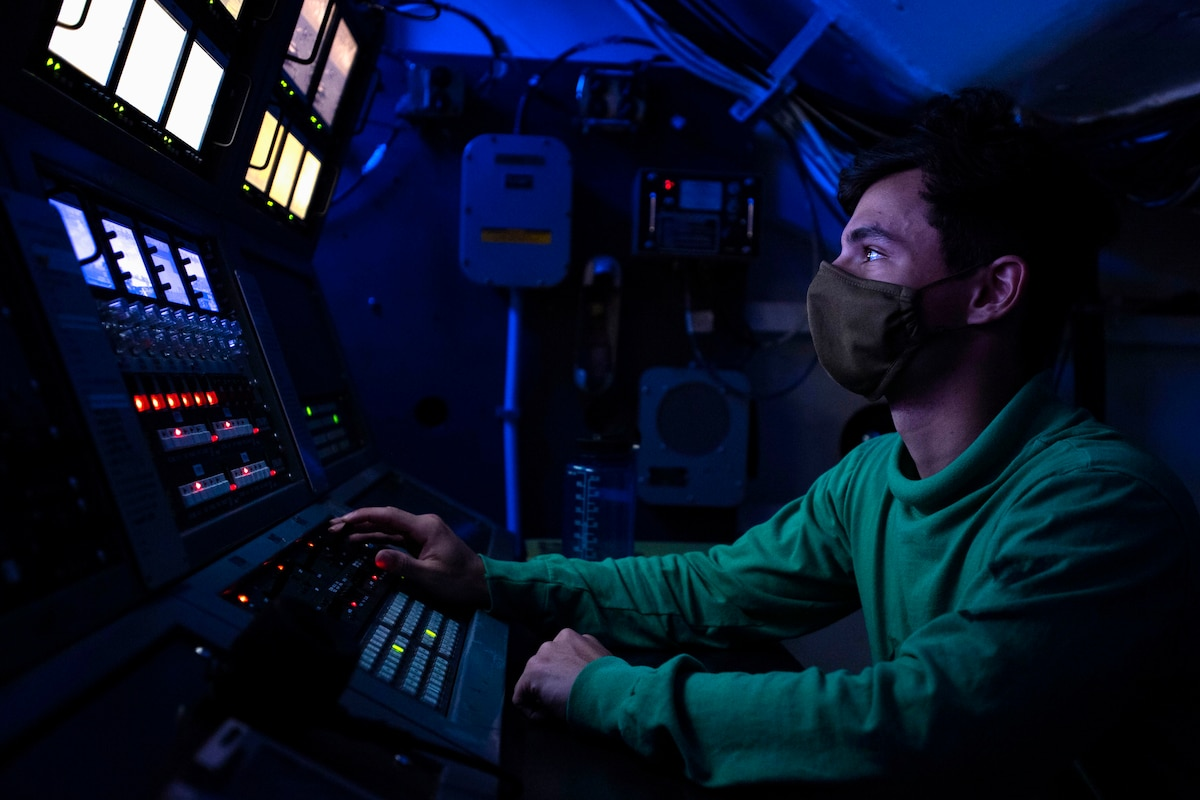 A sailor illuminated by blue light sits in front of monitors.
