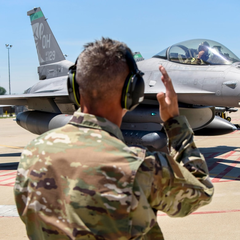 A service member directs a jet.