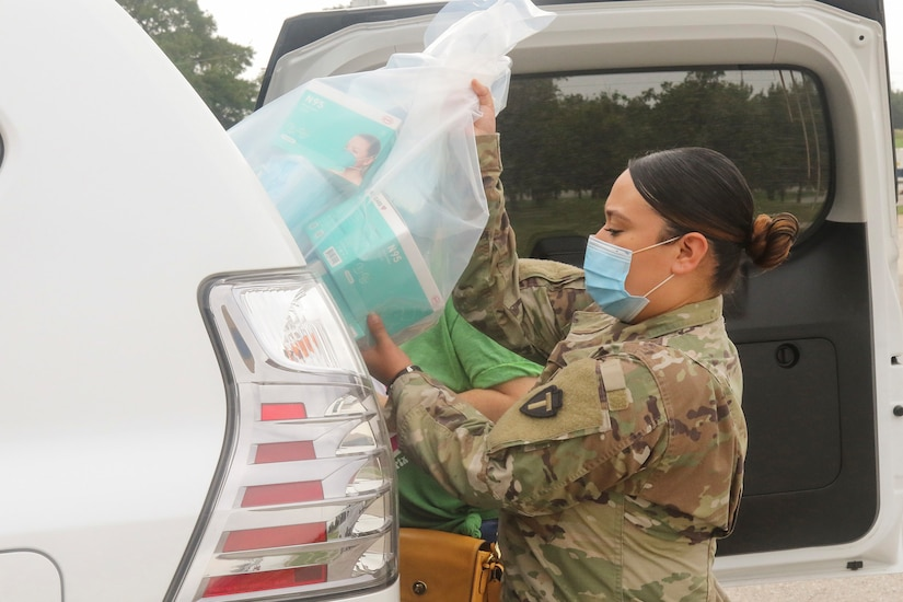 A soldier loads medical supplies into a vehicle.