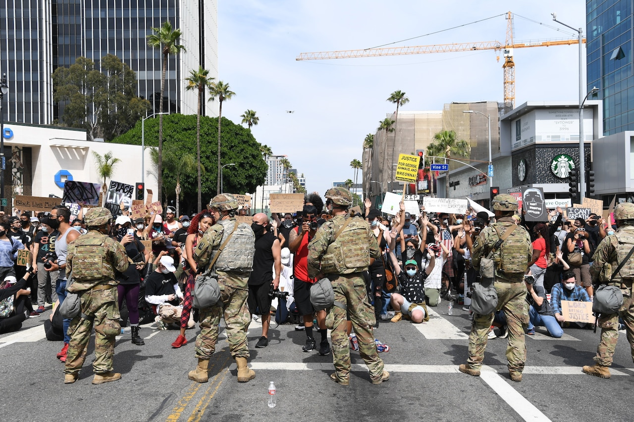Service members stand in front of protesters.