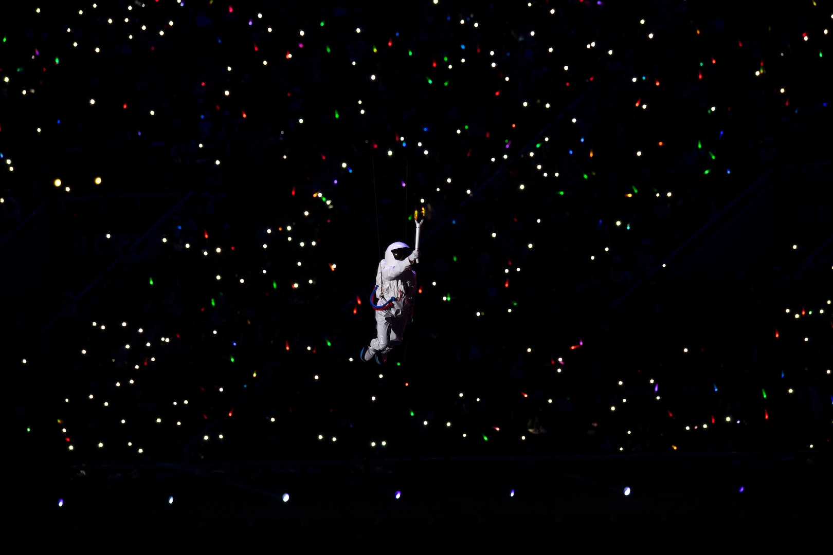 An entertainer floats by wire past a crowd holding light sticks during opening ceremonies for the 2019 CISM Military World Games in Wuhan, China Oct. 18, 2019. Teams from more than 100 countries will compete in dozens of sporting events through Oct. 28. (DoD photo by EJ Hersom)