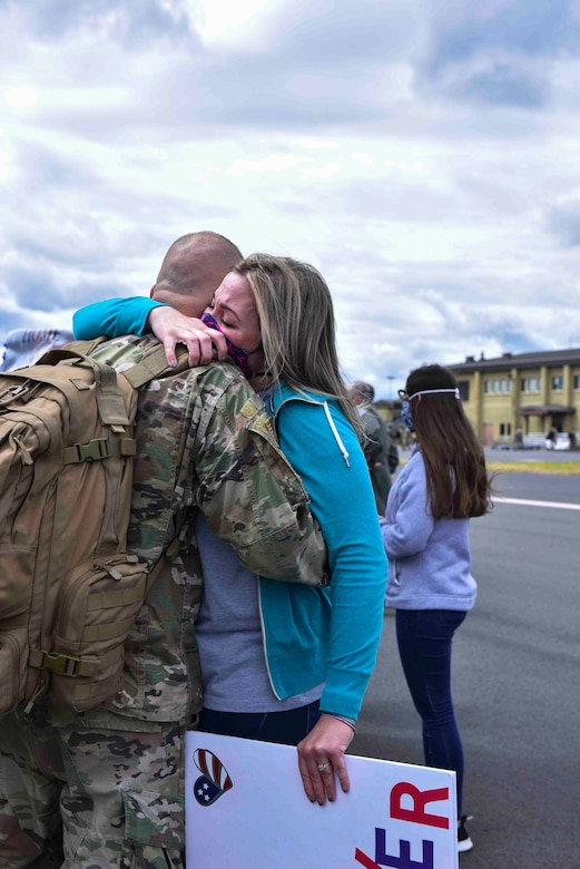 A 93rd Air Refueling Squadron member arrives home from a deployment and is greeted by a loved one on Fairchild Air Force Base, Washington, July 1, 2020. The Airmen left home for a four-month deployment but due to coronavirus disease 2019 health and safety restrictions, members returned after seven months. (U.S. Air Force photo by Airman 1st Class Kiaundra Miller)